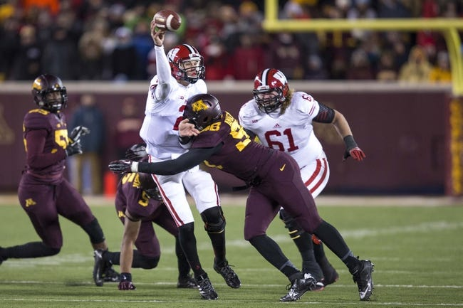 Nov 23, 2013; Minneapolis, MN, USA; Wisconsin Badgers quarterback Joel Stave (2) throws the ball as he gets hit by Minnesota Golden Gophers defensive lineman Michael Amaefula (98) in the second half at TCF Bank Stadium. The Badgers won 20-7. Mandatory Credit: Jesse Johnson-USA TODAY Sports