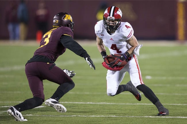 Nov 23, 2013; Minneapolis, MN, USA; Wisconsin Badgers wide receiver Jared Abbrederis (4) attempts to get around Minnesota Golden Gophers defensive back Martez Shabazz (3) in the second half at TCF Bank Stadium. The Badgers won 20-7. Mandatory Credit: Jesse Johnson-USA TODAY Sports