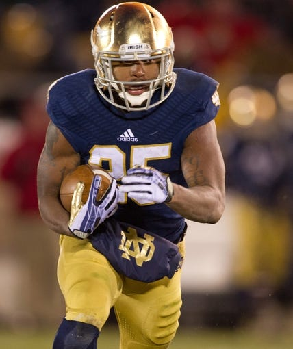 Nov 23, 2013; South Bend, IN, USA; Notre Dame Fighting Irish running back Tarean Folston (25) carries the ball in the third quarter against the BYU Cougars at Notre Dame Stadium. Notre Dame won 23-13. Mandatory Credit: Matt Cashore-USA TODAY Sports