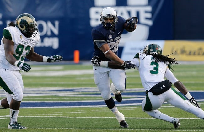 Nov 23, 2013; Logan, UT, USA; Utah State Aggies running back Joey DeMartino (28) breaks through a tackle by Colorado State Rams cornerback Shaq Bell (3) in the fourth quarter at Romney Stadium. Utah State Aggies won 13-0. Mandatory Credit: Chris Nicoll-USA TODAY Sports