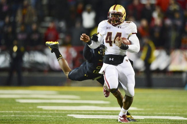 Nov 23, 2013; College Park, MD, USA;  Boston College Eagles running back Andre Williams (44) attempts to break free from a diving Maryland Terrapins defensive back Sean Davis (21) during the fourth quarter at Byrd Stadium. Boston College Eagles defeated Maryland Terrapins 29-26. Mandatory Credit: Tommy Gilligan-USA TODAY Sports
