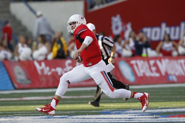Nov 23, 2013; Fresno, CA, USA; Fresno State Bulldogs quarterback Derek Carr (4) runs the ball against the New Mexico Lobos in the third quarter at Bulldog Stadium. The Bulldogs defeated the Lobos 69-28. Mandatory Credit: Cary Edmondson-USA TODAY Sports