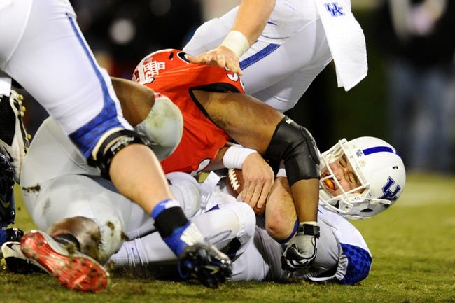 Nov 23, 2013; Athens, GA, USA; Kentucky Wildcats quarterback Maxwell Smith (11) is sacked by Georgia Bulldogs defensive end Garrison Smith (56) during the second half at Sanford Stadium. Georgia defeated Kentucky 59-17. Mandatory Credit: Dale Zanine-USA TODAY Sports