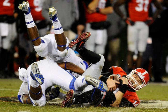 Nov 23, 2013; Athens, GA, USA; Georgia Bulldogs quarterback Hutson Mason (14) recovers a bad snap from center under two Kentucky Wildcats defenders during the second half at Sanford Stadium. Georgia defeated Kentucky 59-17. Mandatory Credit: Dale Zanine-USA TODAY Sports