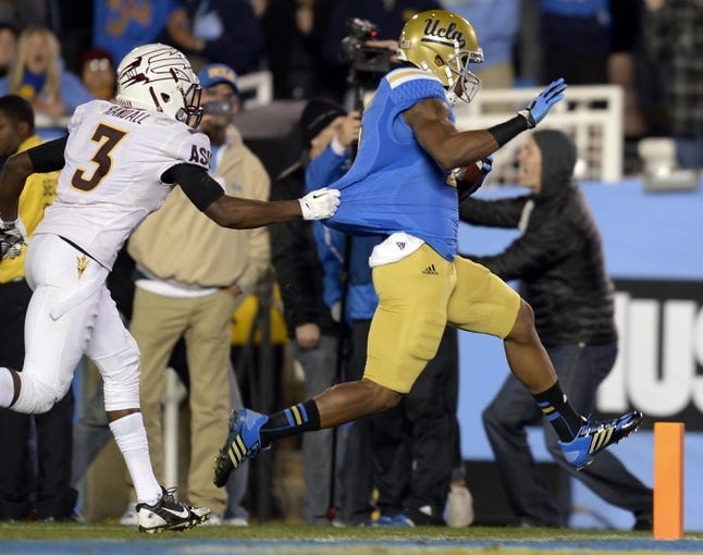 Nov 23, 2013; Pasadena, CA, USA; Arizona State Sun Devils defensive back Damarious Randall (3) tries to tackle UCLA Bruins wide receiver Shaquelle Evans (1) but he cannot stop him from crossing the goal line during the second half at Rose Bowl. Mandatory Credit: Robert Hanashiro-USA TODAY Sports