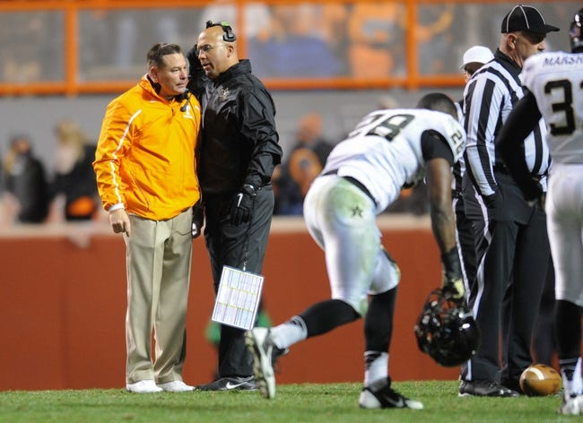 Nov 23, 2013; Knoxville, TN, USA; Tennessee Volunteers head coach Butch Jones and Vanderbilt Commodores head coach James Franklin meet on the field while injured Vanderbilt Commodores defensive back Steven Clarke (12) is attended to at Neyland Stadium. Vanderbilt won 14 to 10. Mandatory Credit: Randy Sartin-USA TODAY Sports