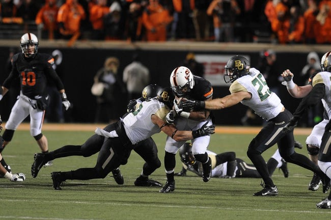Nov 23, 2013; Stillwater, OK, USA; Oklahoma State Cowboys running back Jeremy Smith (31) runs the ball against Baylor Bears linebacker Eddie Lackey (5) and Bears linebacker Brody Trahan (15) at Boone Pickens Stadium. Mandatory Credit: Mark D. Smith-USA TODAY Sports