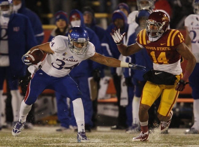Nov 23, 2013; Ames, IA, USA; Kansas Jayhawks running back Connor Embree (34) slips on the frozen turf against the Iowa State Cyclones defender Jared Brackens (14) in the fourth quarter at Jack Trice Stadium. Iowa State won 34-0. Mandatory Credit: Bruce Thorson-USA TODAY Sports