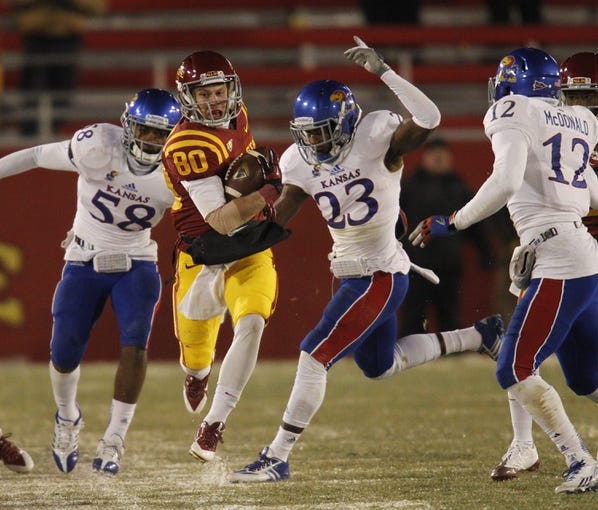 Nov 23, 2013; Ames, IA, USA; Iowa State Cyclones receiver Justin Coleman (80) catches a pass against the Kansas Jayhawks defenders Courtney Arnick (58) and Dexter Linton (23) in the third quarter at Jack Trice Stadium. Iowa State won 34-0. Mandatory Credit: Bruce Thorson-USA TODAY Sports