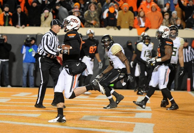 Nov 23, 2013; Stillwater, OK, USA; Oklahoma State Cowboys quarterback Clint Chelf (10) runs for touchdown against the Baylor Bears at Boone Pickens Stadium. Mandatory Credit: Mark D. Smith-USA TODAY Sports