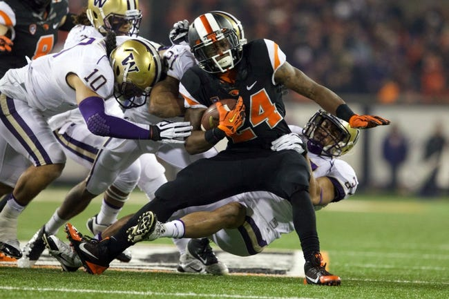 Nov 23, 2013; Corvallis, OR, USA; Washington Huskies linebacker John Timu (10) defensive back Marcus Peters (21) and  linebacker Princeton Fuimaono (37) tackle Oregon State Beavers running back Storm Woods (24) in the first half at Reser Stadium. Mandatory Credit: Jaime Valdez-USA TODAY Sports
