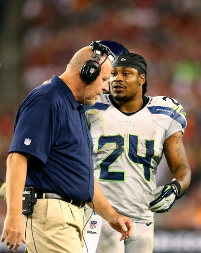 Oct 17, 2013; Phoenix, AZ, USA; Seattle Seahawks offensive line coach Tom Cable (left) talks to running back Marshawn Lynch (24) against the Arizona Cardinals at University of Phoenix Stadium. Mandatory Credit: Mark J. Rebilas-USA TODAY Sports