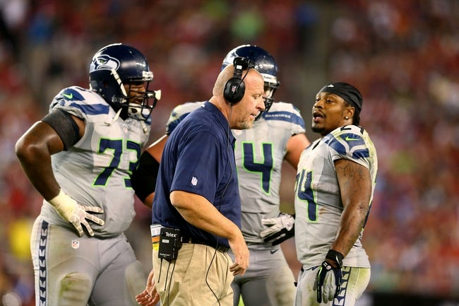 Oct 17, 2013; Phoenix, AZ, USA; Seattle Seahawks offensive line coach Tom Cable (center) talks to running back Marshawn Lynch (24) against the Arizona Cardinals at University of Phoenix Stadium. Mandatory Credit: Mark J. Rebilas-USA TODAY Sports