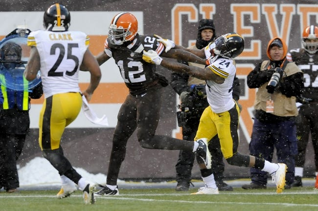 Nov 24, 2013; Cleveland, OH, USA; Cleveland Browns wide receiver Josh Gordon (12) runs the ball past Pittsburgh Steelers cornerback Ike Taylor (24) during the fourth quarter at FirstEnergy Stadium. The Steelers beat the Browns 27-11. Mandatory Credit: Ken Blaze-USA TODAY Sports
