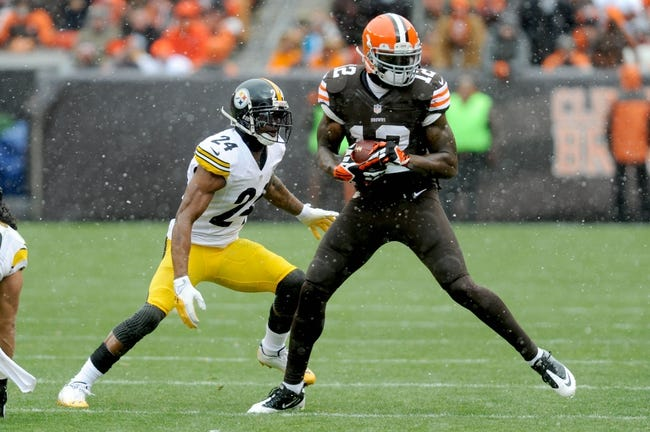 Nov 24, 2013; Cleveland, OH, USA; Cleveland Browns wide receiver Josh Gordon (12) makes a catch ahead of Pittsburgh Steelers cornerback Ike Taylor (24) during the second quarter at FirstEnergy Stadium. Mandatory Credit: Ken Blaze-USA TODAY Sports