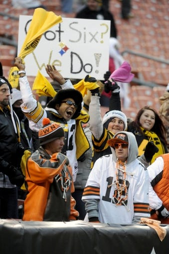 Nov 24, 2013; Cleveland, OH, USA; Pittsburgh Steelers fans celebrate behind Cleveland Browns fans during the fourth quarter at FirstEnergy Stadium. The Steelers beat the Browns 27-11. Mandatory Credit: Ken Blaze-USA TODAY Sports
