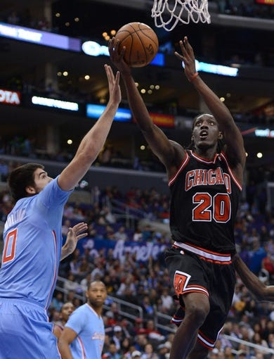Nov 24, 2013; Los Angeles, CA, USA;  Los Angeles Clippers center Byron Mullens (0) defends a shot by Chicago Bulls small forward Tony Snell (20) in the second half of the game at Staples Center. Clippers won 121-82. Mandatory Credit: Jayne Kamin-Oncea-USA TODAY Sports