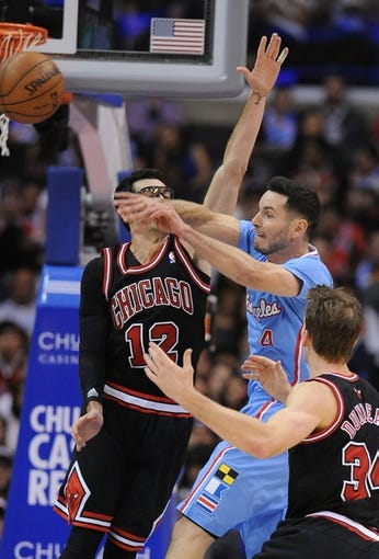 Nov 24, 2013; Los Angeles, CA, USA;  Chicago Bulls shooting guard Kirk Hinrich (12) defends a pass by Los Angeles Clippers shooting guard J.J. Redick (4) in the second half the game at Staples Center. Clippers won 121-82. Mandatory Credit: Jayne Kamin-Oncea-USA TODAY Sports