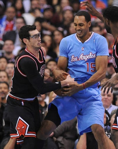 Nov 24, 2013; Los Angeles, CA, USA;  Chicago Bulls shooting guard Kirk Hinrich (12) and Los Angeles Clippers center Ryan Hollins (15) battle for a jump ball in the second half the game at Staples Center. Clippers won 121-82. Mandatory Credit: Jayne Kamin-Oncea-USA TODAY Sports
