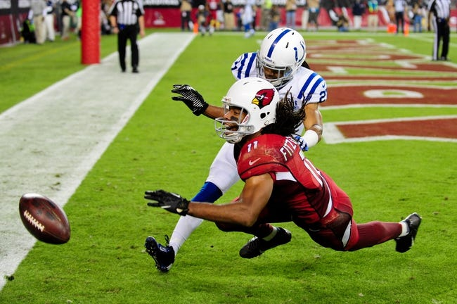 Nov 24, 2013; Phoenix, AZ, USA; Arizona Cardinals wide receiver Larry Fitzgerald (11) misses catching the ball as Indianapolis Colts defensive back Josh Gordy (27) defends during the second half at University of Phoenix Stadium. Mandatory Credit: Matt Kartozian-USA TODAY Sports