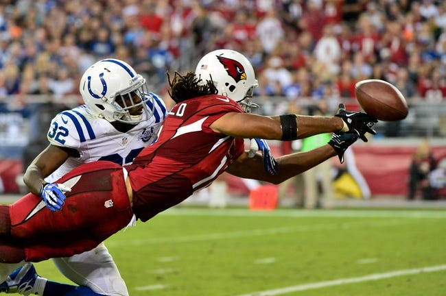 Nov 24, 2013; Phoenix, AZ, USA; Arizona Cardinals wide receiver Larry Fitzgerald (11) and Indianapolis Colts cornerback Cassius Vaughn (32) attempt to catch a ball during the second half at University of Phoenix Stadium. Mandatory Credit: Matt Kartozian-USA TODAY Sports