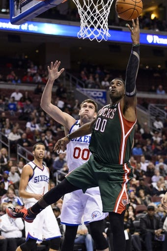 Nov 22, 2013; Philadelphia, PA, USA; Milwaukee Bucks guard O.J. Mayo (00) shoots as Philadelphia 76ers center Spencer Hawes (00) defends during the third quarter at Wells Fargo Center. The Sixers defeated the Bucks 115-107 in overtime. Mandatory Credit: Howard Smith-USA TODAY Sports