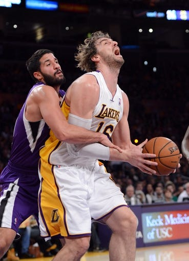 Nov 24, 2013; Los Angeles, CA, USA;  Los Angeles Lakers center Pau Gasol (16) is fouled by Sacramento Kings point guard Greivis Vasquez (10) during the game at Staples Center. Lakers won 100-86. Mandatory Credit: Jayne Kamin-Oncea-USA TODAY Sports