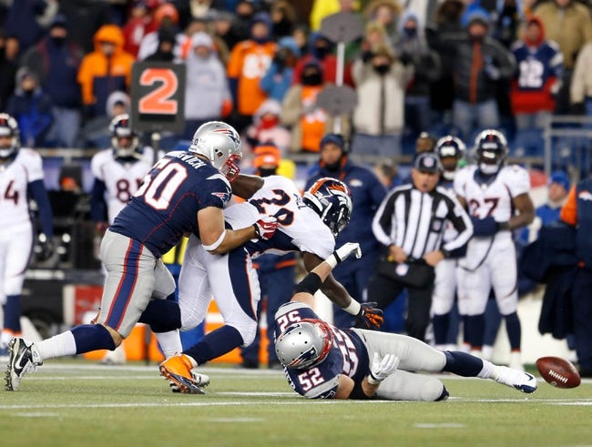 Nov 24, 2013; Foxborough, MA, USA; Denver Broncos running back Montee Ball (28) fumbles the ball against New England Patriots linebacker Dane Fletcher (52) and defensive end Rob Ninkovich (50) in the third quarter at Gillette Stadium. The New England Patriots defeated the Denver Broncos 34-31. Mandatory Credit: David Butler II-USA TODAY Sports