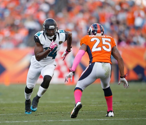 Oct 13, 2013; Denver, CO, USA; Jacksonville Jaguars wide receiver Justin Blackmon (14) runs a route against Denver Broncos cornerback Chris Harris Jr. (25) during the game at Sports Authority Field at Mile High. Mandatory Credit: Chris Humphreys-USA TODAY Sports