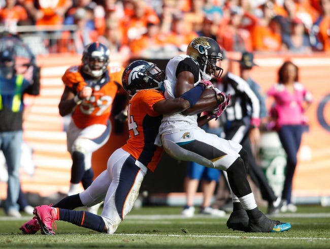 Oct 13, 2013; Denver, CO, USA; Jacksonville Jaguars wide receiver Justin Blackmon (right) is tackled by Denver Broncos cornerback Champ Bailey (left) during the game at Sports Authority Field at Mile High. Mandatory Credit: Chris Humphreys-USA TODAY Sports