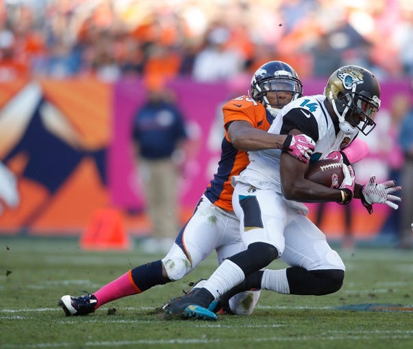Oct 13, 2013; Denver, CO, USA; Jacksonville Jaguars wide receiver Justin Blackmon (14) is tackled by cornerback Quentin Jammer (23)  during the game at Sports Authority Field at Mile High. Mandatory Credit: Chris Humphreys-USA TODAY Sports