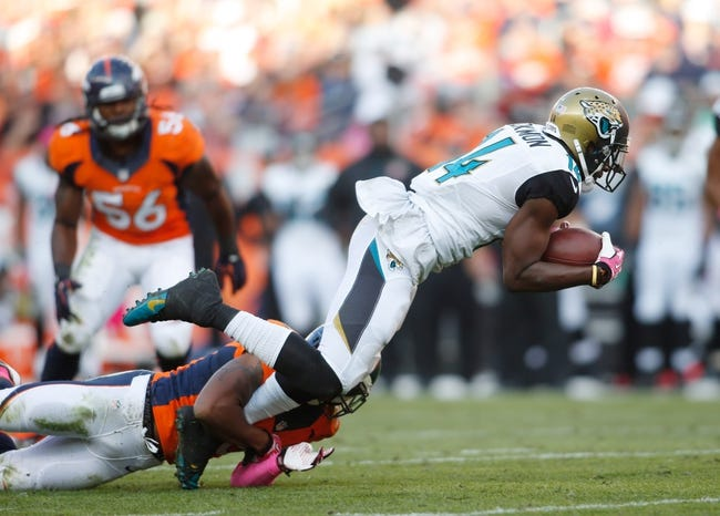 Oct 13, 2013; Denver, CO, USA; Jacksonville Jaguars wide receiver Justin Blackmon (14) tackled by Denver Broncos cornerback Chris Harris Jr. (25) during the game at Sports Authority Field at Mile High. Mandatory Credit: Chris Humphreys-USA TODAY Sports