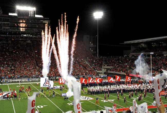 Nov 9, 2013; Tucson, AZ, USA; Arizona Wildcats cheerleaders and band members lead the team entry before the first quarter against the UCLA Bruins at Arizona Stadium. Mandatory Credit: Casey Sapio-USA TODAY Sports