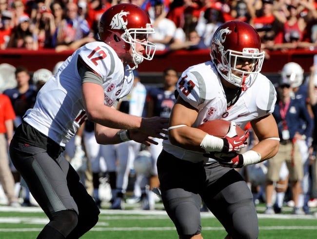 Nov 16, 2013; Tucson, AZ, USA; Washington State Cougars quarterback Connor Halliday (12) hands off to running back Jeremiah Laufasa (43) during the first quarter against the Arizona Wildcats at Arizona Stadium. The Cougars beat the Wildcats 24-17. Mandatory Credit: Casey Sapio-USA TODAY Sports
