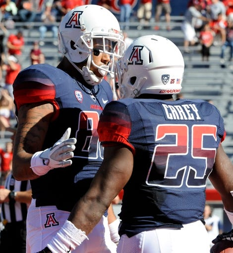 Nov 16, 2013; Tucson, AZ, USA; Arizona Wildcats running back Ka  Deem Carey (25) is congratulated by receiver David Richards (80) after scoring a touchdown against the Washington State Cougars during the second quarter at Arizona Stadium. The Cougars beat the Wildcats 24-17. Mandatory Credit: Casey Sapio-USA TODAY Sports