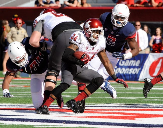 Nov 16, 2013; Tucson, AZ, USA; Washington State Cougars running back Teondray Caldwell (34) runs the ball as he is pursued by Arizona Wildcats linebacker Marquis Flowers (2) during the first quarter at Arizona Stadium. The Cougars beat the Wildcats 24-17. Mandatory Credit: Casey Sapio-USA TODAY Sports