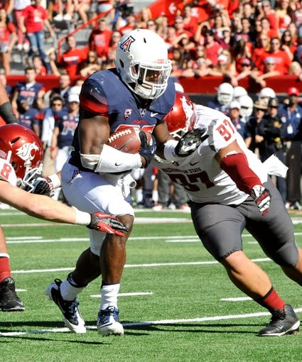 Nov 16, 2013; Tucson, AZ, USA; Arizona Wildcats running back Ka  Deem Carey (25) runs the ball as he is pursued by Washington State Cougars defensive lineman Destiny Vaeao (97) during the second quarter at Arizona Stadium. The Cougars beat the Wildcats 24-17. Mandatory Credit: Casey Sapio-USA TODAY Sports