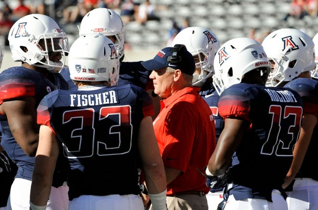 Nov 16, 2013; Tucson, AZ, USA; Arizona Wildcats defensive coordinator Jeff Casteel talks strategy with linebacker Jake Fischer (33) and cornerback Devin Holiday (13) in a huddle during the fourth quarter against the Washington State Cougars at Arizona Stadium. The Cougars beat the Wildcats 24-17. Mandatory Credit: Casey Sapio-USA TODAY Sports