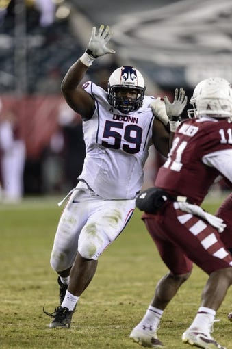 Nov 23, 2013; Philadelphia, PA, USA; Connecticut Huskies defensive tackle Shamar Stephen (59) looks to sack Temple Owls quarterback P.J. Walker (11) during the second quarter at Lincoln Financial Field. UCONN defeated Temple 28-21. Mandatory Credit: Howard Smith-USA TODAY Sports