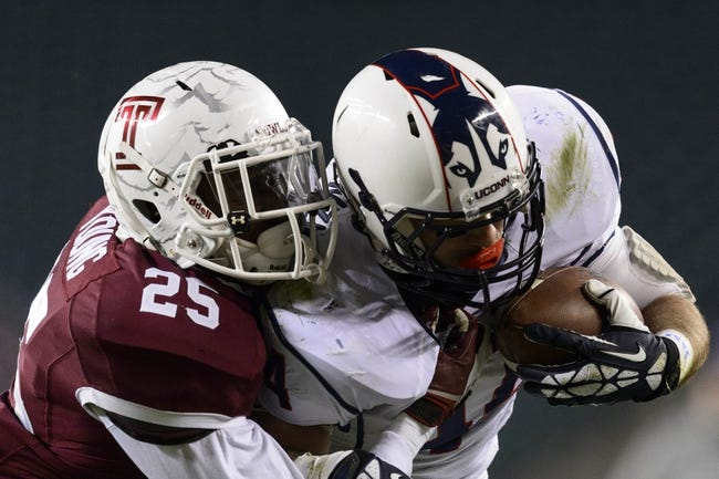 Nov 23, 2013; Philadelphia, PA, USA; Temple Owls defensive back Tavon Young (25) tackles Connecticut Huskies running back Max DeLorenzo (44) during the fourth quarter at Lincoln Financial Field. UCONN defeated Temple 28-21. Mandatory Credit: Howard Smith-USA TODAY Sports