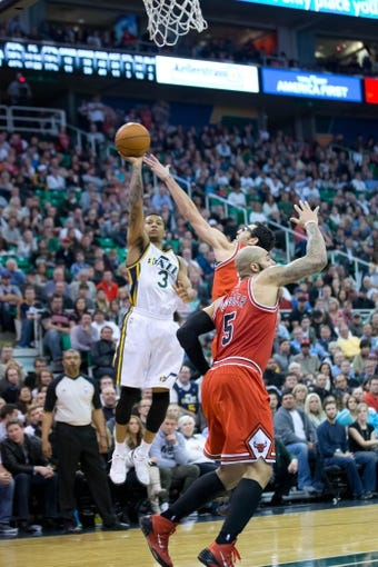 Nov 25, 2013; Salt Lake City, UT, USA; Utah Jazz point guard Trey Burke (3) shoots over Chicago Bulls shooting guard Kirk Hinrich (12) during the second half at EnergySolutions Arena. The Jazz won 89-83 in overtime. Mandatory Credit: Russ Isabella-USA TODAY Sports