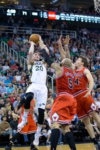 Nov 25, 2013; Salt Lake City, UT, USA; Utah Jazz shooting guard Gordon Hayward (20) shoots over Chicago Bulls power forward Carlos Boozer (5) and guard Mike Dunleavy (34) during the second half at EnergySolutions Arena. The Jazz won 89-83 in overtime. Mandatory Credit: Russ Isabella-USA TODAY Sports