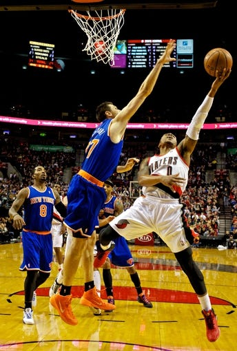 Nov 25, 2013; Portland, OR, USA; Portland Trail Blazers point guard Damian Lillard (0) shots over New York Knicks power forward Andrea Bargnani (77) at the Moda Center. Mandatory Credit: Craig Mitchelldyer-USA TODAY Sports