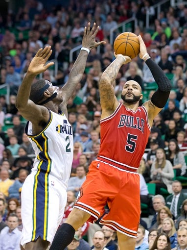 Nov 25, 2013; Salt Lake City, UT, USA; Chicago Bulls power forward Carlos Boozer (5) shoots over Utah Jazz power forward Marvin Williams (2) during the overtime period at EnergySolutions Arena. The Jazz won 89-83 in overtime. Mandatory Credit: Russ Isabella-USA TODAY Sports