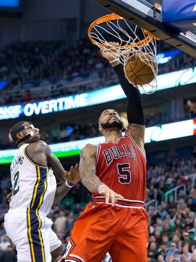 Nov 25, 2013; Salt Lake City, UT, USA; Chicago Bulls power forward Carlos Boozer (5) dunks in front of Utah Jazz power forward Marvin Williams (2) during the overtime period at EnergySolutions Arena. The Jazz won 89-83 in overtime. Mandatory Credit: Russ Isabella-USA TODAY Sports
