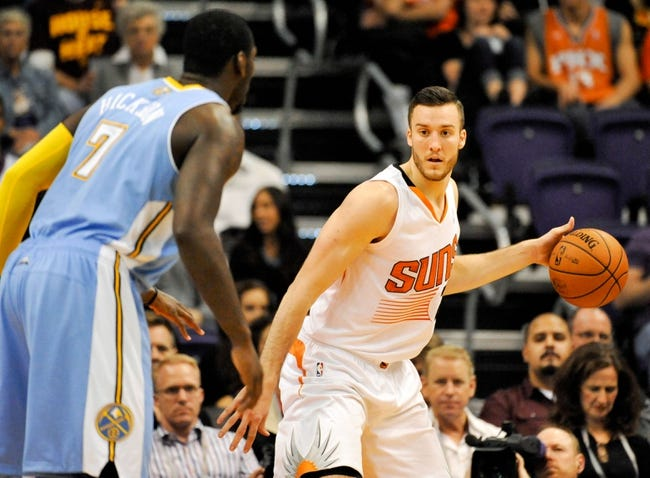 Nov 8, 2013; Phoenix, AZ, USA; Phoenix Suns power forward Miles Plumlee (22) dribbles the ball as he is defended by Denver Nuggets power forward J.J. Hickson (7) during the second quarter at US Airways Center. Mandatory Credit: Casey Sapio-USA TODAY Sports