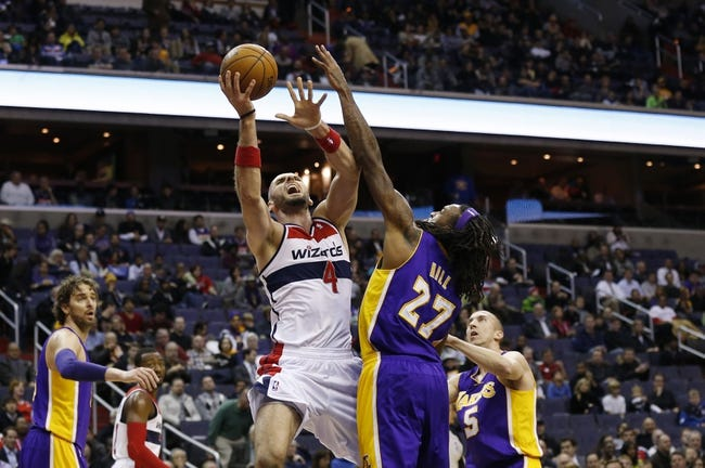 Nov 26, 2013; Washington, DC, USA; Washington Wizards center Marcin Gortat (4) shoots the ball as Los Angeles Lakers center Jordan Hill (27) defends in the first quarter at Verizon Center. Mandatory Credit: Geoff Burke-USA TODAY Sports
