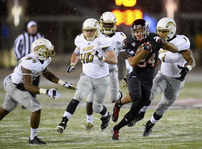 Nov 26, 2013; DeKalb, IL, USA; Northern Illinois Huskies running back James Spencer (34) rushes the ball against Western Michigan Broncos cornerback Donald Celiscar (34) during the first quarter at Huskie Stadium. Mandatory Credit: Mike DiNovo-USA TODAY Sports