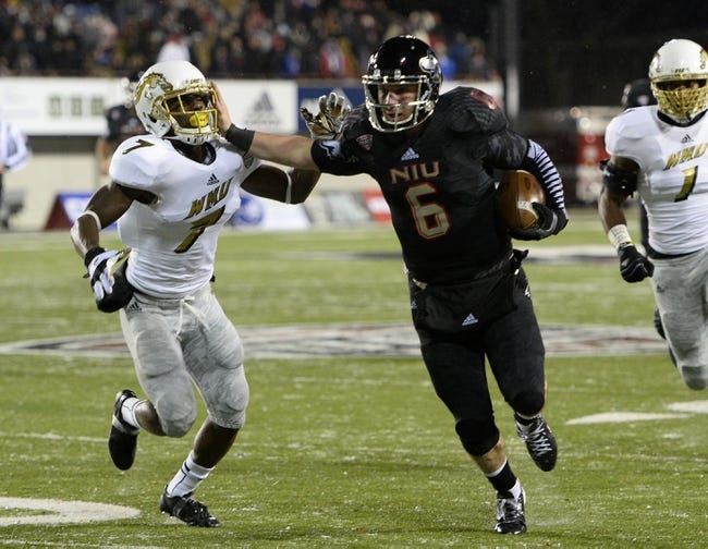 Nov 26, 2013; DeKalb, IL, USA; Northern Illinois Huskies quarterback Jordan Lynch (6) rushes for a touchdown against Western Michigan Broncos cornerback Ronald Zamort (7) during the second quarter at Huskie Stadium. Mandatory Credit: Mike DiNovo-USA TODAY Sports