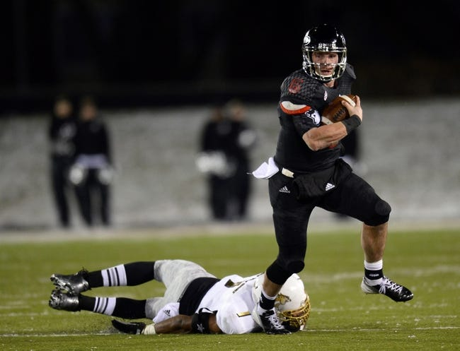 Nov 26, 2013; DeKalb, IL, USA; Northern Illinois Huskies quarterback Jordan Lynch (6) breaks the tackle of Western Michigan Broncos linebacker Mike Jones (1) during the third quarter at Huskie Stadium. Mandatory Credit: Mike DiNovo-USA TODAY Sports